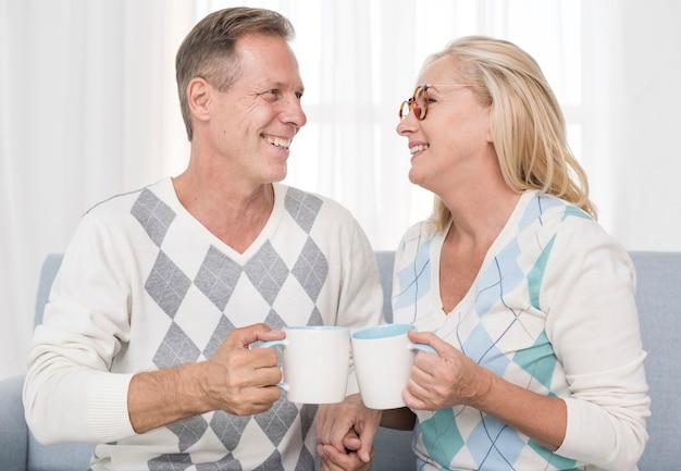 Tiro médio casal feliz segurando canecas brancas