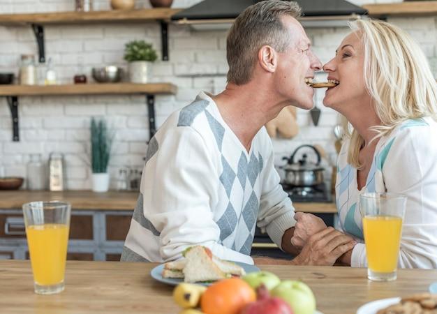 Tiro médio casal fofo, compartilhando um biscoito