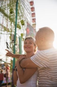 Tiro médio casal olhando um ao outro no parque temático
