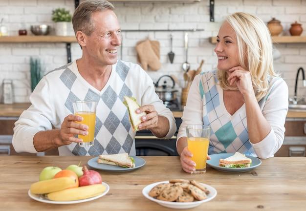Tiro médio casal sorridente na cozinha tomando café da manhã