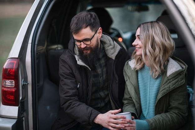 Tiro médio casal sorridente na van