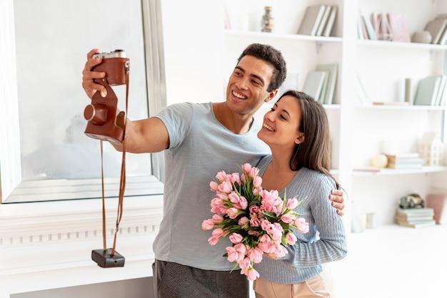 Tiro médio casal sorridente tirando uma foto