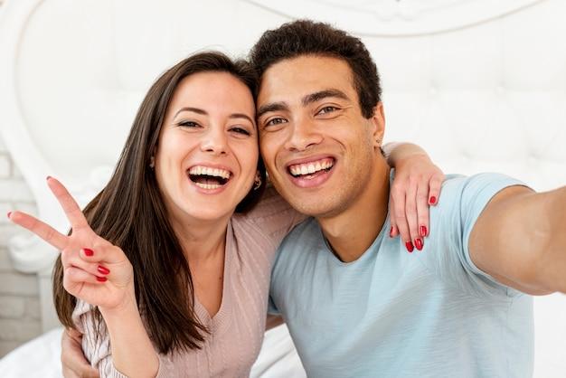 Tiro médio casal sorridente tomando uma selfie