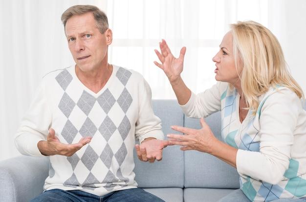 Tiro médio chateado casal discutindo no sofá