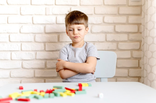 Tiro médio chateado menino na cadeira