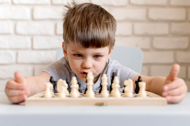 Tiro médio criança jogando xadrez