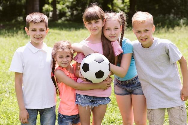 Tiro médio, crianças, posar, e, olhando câmera