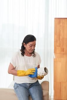 Tiro médio da empregada doméstica profissional, limpando o vaso de flor