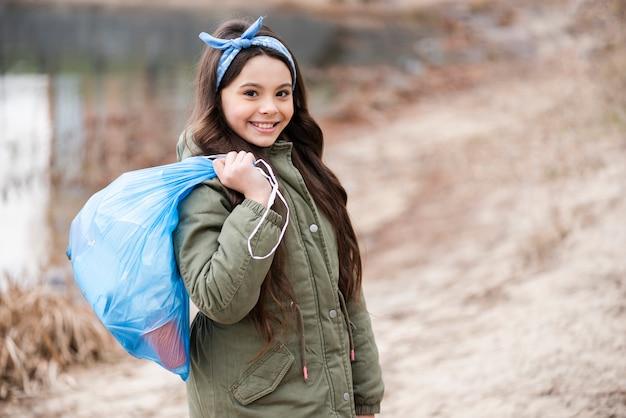 Tiro médio da garota segurando o saco de plástico