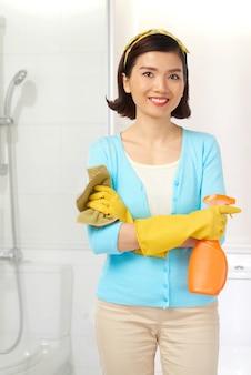Tiro médio da jovem governanta asiática posando durante a limpeza do banheiro