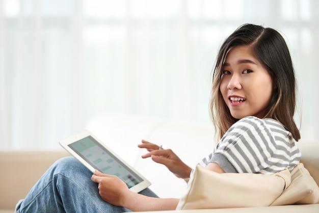 Tiro médio da jovem menina asiática, virando-se para olhar para a câmera distraída do seu tablet pc