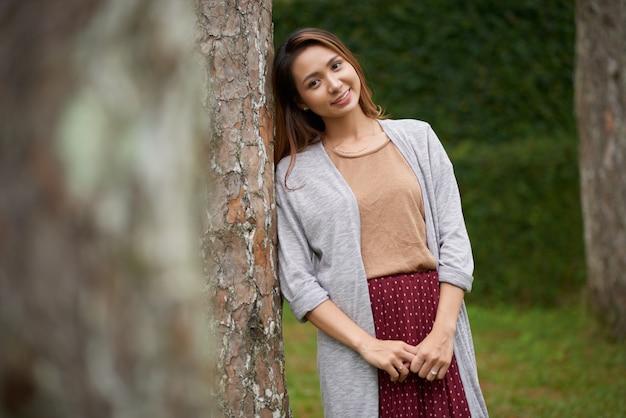 Tiro médio da jovem mulher asiática, apoiando-se na árvore e posando para uma foto no parque