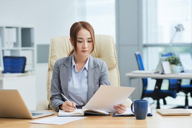 Tiro médio da jovem mulher asiática em terno sentado na mesa no escritório e ler o documento