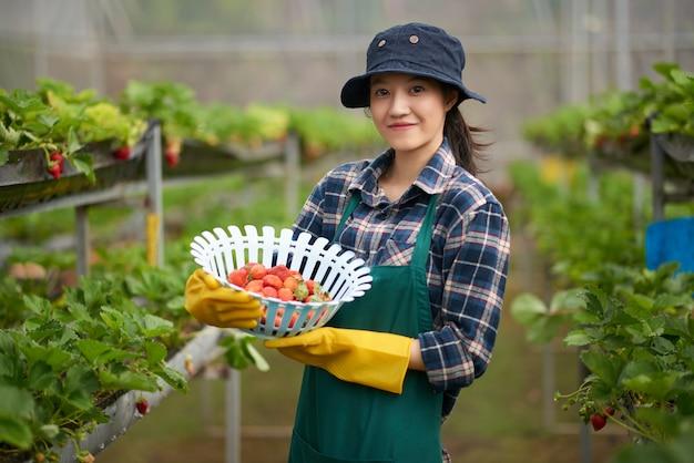 Tiro médio da jovem mulher asiática no agricultor em geral, segurando uma cesta de morangos maduros
