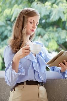 Tiro médio da jovem mulher loira em pé na varanda com uma xícara de café e tablet pc lendo