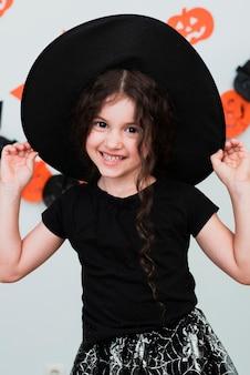Tiro médio da menina bonitinha com chapéu de bruxa