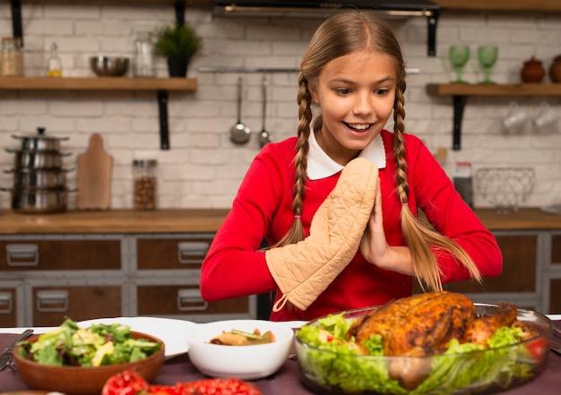 Tiro médio da menina pronta para comer o peru de ação de graças