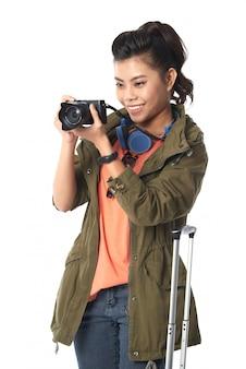 Tiro médio da mulher asiática, segurando uma câmera fotográfica tirando foto