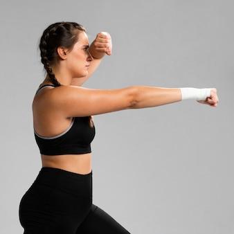 Tiro médio da mulher de karatê lateral exercitando