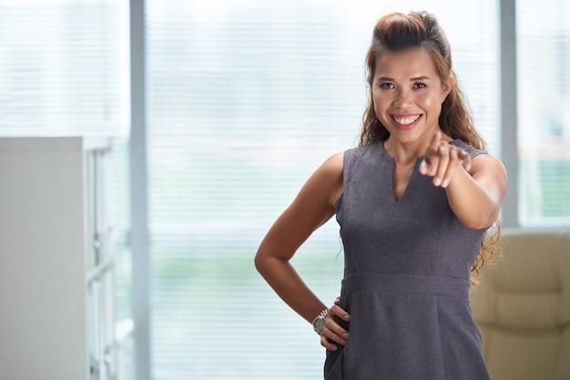 Tiro médio da mulher de negócios, apontando para a câmera e sorrindo