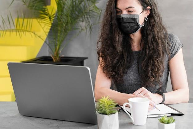 Tiro médio da mulher de negócios usando máscara médica dentro
