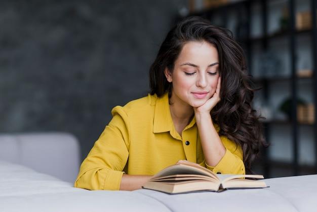 Tiro médio da mulher do smiley que lê