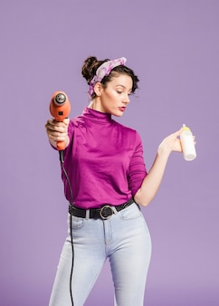 Tiro médio da mulher prática segurando broca e mamadeira vista frontal