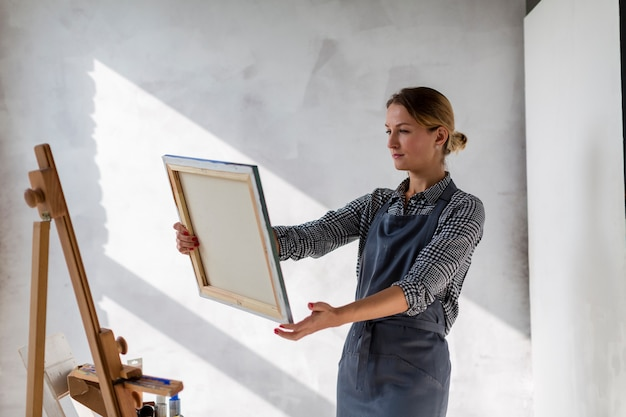 Tiro médio da mulher segurando a lona no estúdio