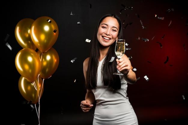 Tiro médio da mulher segurando a taça de champanhe