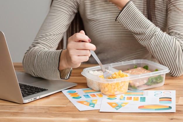 Tiro médio da mulher trabalhando e comendo