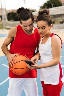 Tiro médio de amigos com bola de basquete