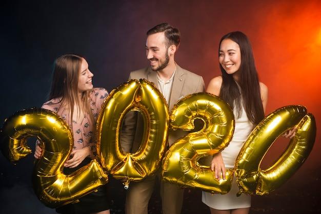 Tiro médio de amigos segurando balões na festa de ano novo