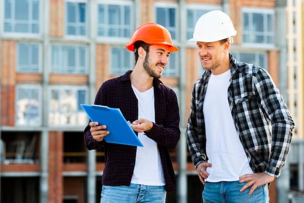 Tiro médio, de, arquiteta, e, engenheiro, supervisionando, construção