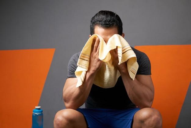 Tiro médio de atleta masculino irreconhecível, limpando o suor com uma toalha sentada no vestiário da academia