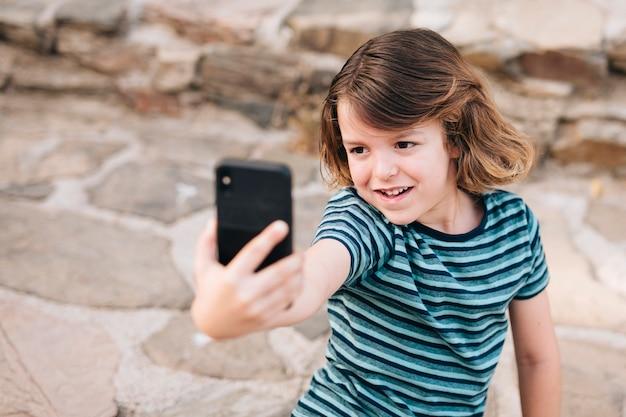 Tiro médio, de, criança, levando, um, selfie