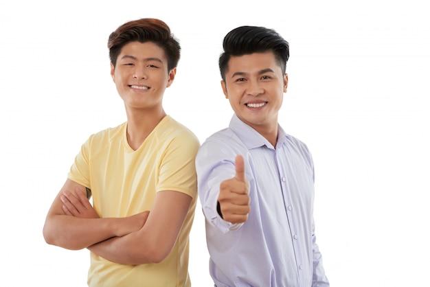 Tiro médio de dois caras em pé ombro a ombro e gesticulando para a câmera