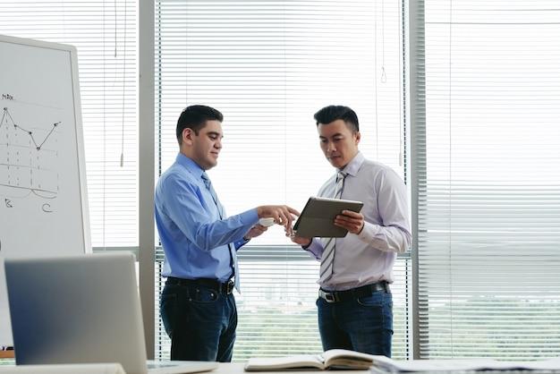 Tiro médio de dois colegas de pé no escritório e discutir dados no tablet pc