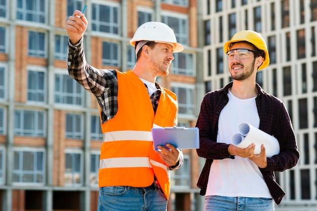 Tiro médio, de, engenheiro, e, arquiteta, supervisionando, construção