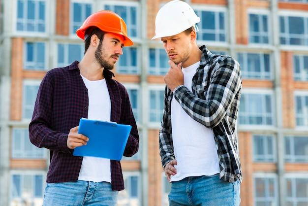 Tiro médio, de, engenheiro, e, trabalhador construção, falando