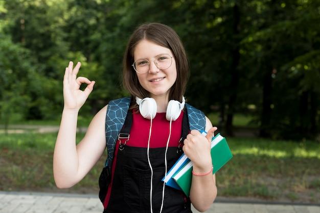 Tiro médio, de, feliz, highschool, menina, segurando, livros, em, mãos