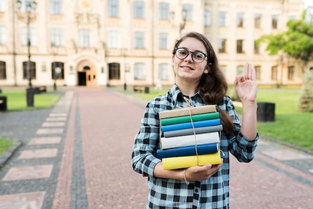 Tiro médio, de, highschool, menina, segurando, livros, em, mãos