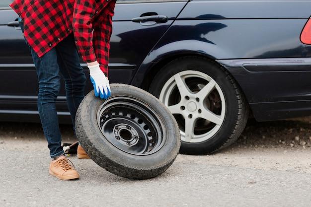 Tiro médio, de, homem, com, sobressalente, pneu