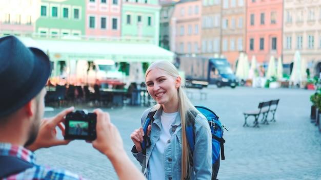 Tiro médio de homem fazendo fotos de turista feminino na vista da praça do mercado da cidade mulher loira ...