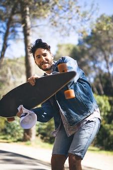 Tiro médio, de, homem, segurando, skateboard