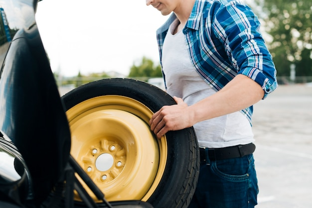 Tiro médio, de, homem, tirando, sobressalente, pneu