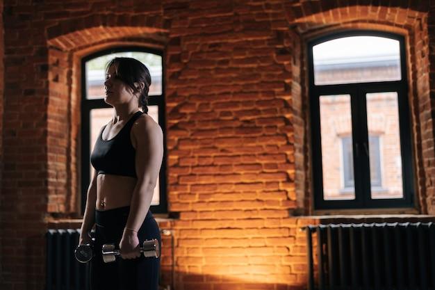 Tiro médio de jovem atlética com belo corpo forte, vestindo roupas esportivas, segurando halteres durante o treinamento de treino. treino feminino de fitness caucasiano fora exercitando-se no ginásio escuro.