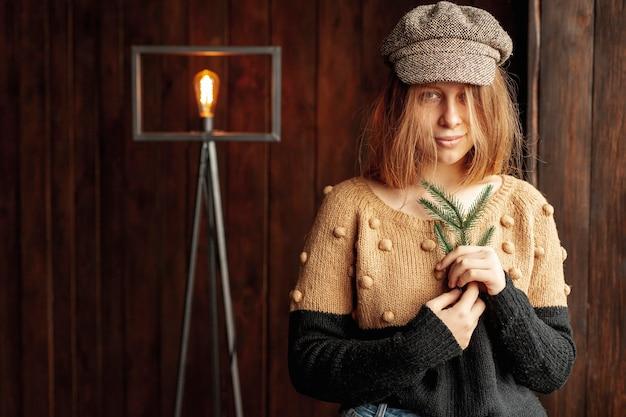 Tiro médio de menina bonita com galho de árvore do abeto e lâmpada
