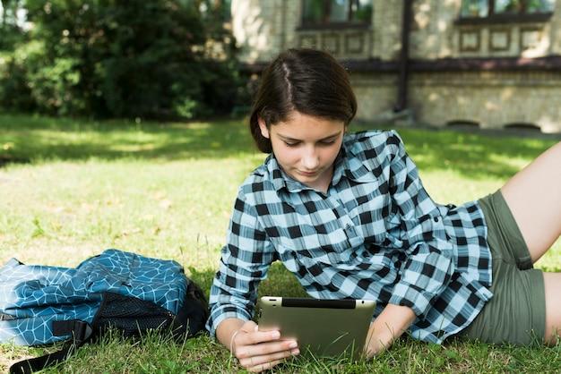 Tiro médio, de, menina escola, usando, tablete, sentando, ligado, gramado