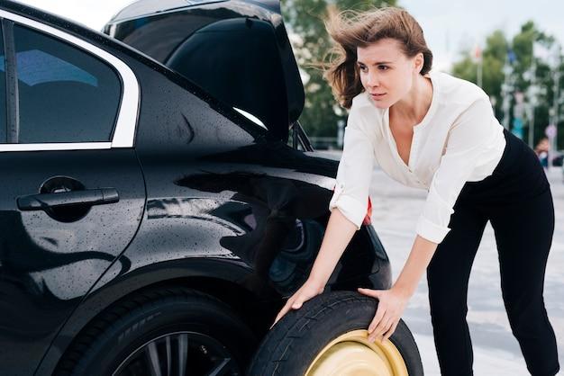 Tiro médio, de, mulher, mudança, pneu