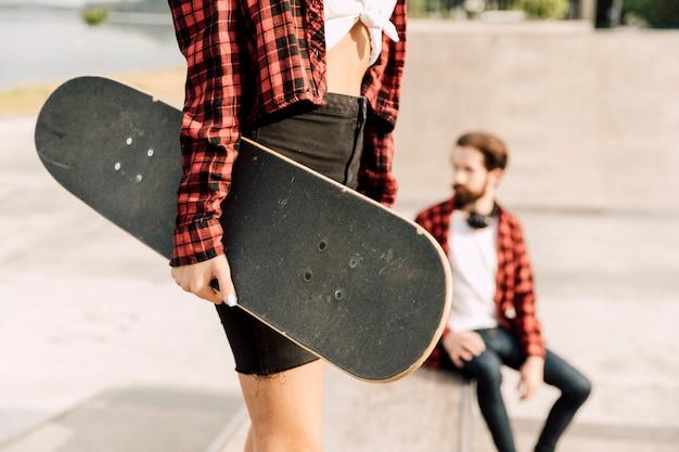 Tiro médio, de, mulher segura, skateboard
